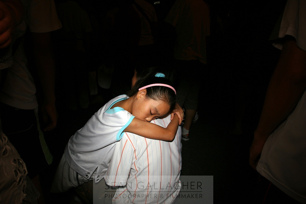 CHINA. Beijing. A young girl rests in her fathers arms in the Olympic village whilst watching rehearsals for the Beijing Olympic games. 2008