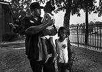 """AOF.FE.062907.EDR.JPG  Rodney Carolina (left), whose 15-year-old nephew Quincy Bowens died in his arms earlier that week, holds his 2-year-old daughter Zyandrea Carolina on Friday, June 29, 2007.  Quincy Bowens was ushering Zyandrea into her South Roxboro St. apartment in Durham when the drive-by shooting took his life.  Kamesha Alston (right), 9, was the oldest of four cousins who witnessed the killing. Rodney Carolina recalls Bowens' last moments, """"He was looking up at me with this expression in his eyes, like 'Help me. Help me.'  It was the first time in my life that I've felt helpless. I felt like losing it,"""" said Carolina. """"I'm asking God to help me lift up my kids, to make me strong for them,"""" he said.  """"I have faith that God will answer their questions. He will make a way for us.""""   Staff photo by Ted Richardson/News & Observer..."""