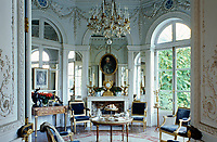 The walls of the Octagonal Salon are covered in ornate plasterwork and the Louis XVI tea table features a cake stand which retracts into the table