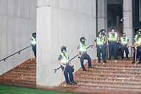 Police stand ready with batons on the steps of Boston City Hall in Boston, Massachusetts, on Fri., Sept. 25, 2020, as protestors marched nearby to demand justice for the police killing of Breonna Taylor after this week's announcement that the Louisville, Kentucky, police officers would not be charged. The group marched from Nubian Square in Roxbury to the Boston Police Department Headquarters and then to downtown Boston. The killing of Breonna Taylor, along with the killing of other people of color by police in 2020 and previously, has led to widespread protest and demonstration throughout the country. This week's decision not to charge the officers in her killing has led to a recharged protest movement in Boston and elsewhere. <br /> <br /> City and state officials stated that they did not want a repeat of the violence of the May 31 protests and stationed police around downtown and had National Guard soldiers ready to respond.