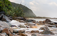 Rocky estuary of tanin stained Mossy Burn with coastal vegetation on beach near Kohaihai and Karamea, Kahurangi National Park, Buller Region, West Coast, New Zealand, NZ