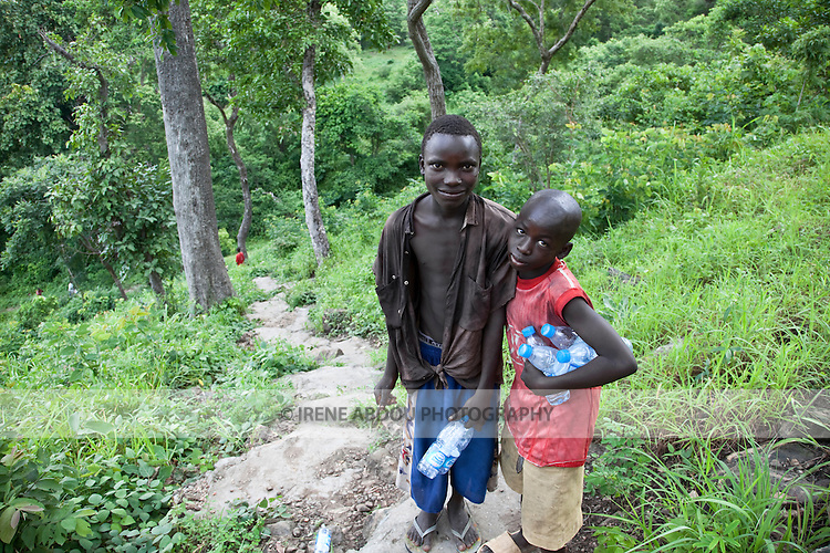 Two boys sell bottled water to visitors at Gurara Falls.  The impressive waterfalls on the Gurara River in Nigeria's Niger State, makes a pleasant day trip and picnic stop from the capital.