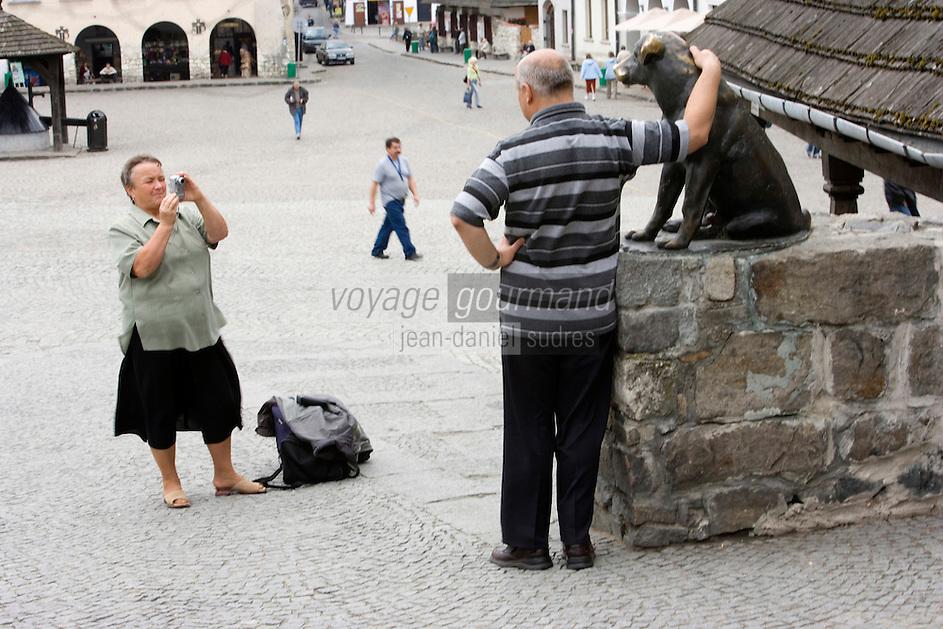 Europe/Pologne/Kazimierz Dolny: -Place du marché-Rynek un couple de touriste polonais se photographie auprés de la statue du chien porte-bonheur