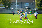 Lixnaw's Eoin Stack on a run as Rory Reen of Tralee Parnells puts in a challenge in the Minor hurling championship quarter final.