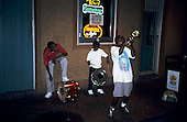 New Orleans, USA. Jazz trio of kids with (1 trumpet, 2 drummers play with neon Heineken and Amstel beer signs in window behind.