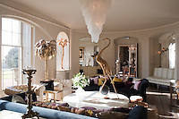 The living room is decorated in a more contemporary style and features a collection of modern sculpture