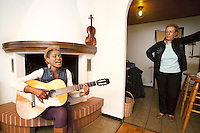 Switzerland. Canton Ticino. Aranno. Orpheline at home. Orpheline is a composer, song writer, a singer and a musician. She sings and plays the guitar while her mother stands up and listens. The violin used to be her father's musical instrument. She is a young woman (24 years old). Her mother is swiss and her father was a black american citizen. Mixed race. Aranno is located in the Malcantone area. 19.03.2010 © 2010 Didier Ruef