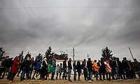 Pictured: A queue of refugees at Idomeni Monday 29 February 2016<br /> Re: A crowd of migrants has burst through a barbed-wire fence on the FYRO Macedonia-Greece border using a steel pole as a battering ram.<br /> TV footage showed migrants pushing against the fence at Idomeni, ripping away barbed wire, as FYRO Macedonian police let off tear gas to force them away.<br /> A section of fence was smashed open with the battering ram. It is not clear how many migrants got through.<br /> Many of those trying to reach northern Europe are Syrian and Iraqi refugees.<br /> About 6,500 people are stuck on the Greek side of the border, as FYRO Macedonia is letting very few in. Many have been camping in squalid conditions for a week or more, with little food or medical help.