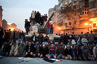 Anti-government protesters answer the evening call to prayer in front of an abandoned army tank amidst violent clashes with pro-Mubarak supporters outside the Egyptian Museum in Tahrir Square. Continued anti-government protests take place in Cairo calling for President Mubarak to stand down. After dissolving the government, Mubarak still refuses to step down from power.