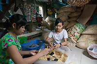 """Ma Phyu*, 14 years, and Ma Thandar*,15 years, packaging dry noodles. They are employed by Nila* and her husband who run a home-based business baking cakes and packaging dry noodles which are sold in local markets. """"We have been working here since we are 12 years old and dropped school at the age of 10. We work about 10 hours a day and support our families who live in a village nearby with our income. We all live together here and share a room upstairs in the house. It´s ok for us to do this work, we don`t find it too tiring."""""""