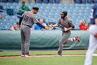 Lehigh Valley IronPigs left fielder Andrew Pullin (15) celebrates with bench coach Wes Helms (18) as he rounds third base after hitting a home run in the top of the seventh inning during a game against the Syracuse Chiefs on May 20, 2018 at NBT Bank Stadium in Syracuse, New York.  Lehigh Valley defeated Syracuse 5-2.  (Mike Janes/Four Seam Images)