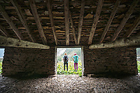 The Via Alta Verzasca is a five day ridge traverse hike above the Valle Verzasca in the Ticino region of Switzerland. Hikers stand outside an old barn on their way down to Sonogno on the last day of the tour.