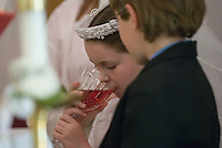 A young girl drinks wine during her first communion sacrament at a Catholic church in Johnstown, OH.<br />