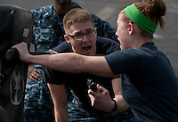120302-N-DR144-142 ARABIAN GULF (March 2, 2012) Master-at-Arms 2nd Class Jonathan Prichard, assigned to the Security Department, motivates Information Systems Technician 2nd Class Tara Smolka as she defends herself against a simulated attacker after being sprayed with Oleoresin Capsicum (OC) spray during a security academy OC spray qualification on the flight deck aboard the Nimitz-class aircraft carrier USS Carl Vinson (CVN 70). Carl Vinson and Carrier Air Wing (CVW) 17 are deployed to the U.S. 5th Fleet area of responsibility.  (U.S. Navy photo by Mass Communication Specialist 2nd Class James R. Evans/Released).