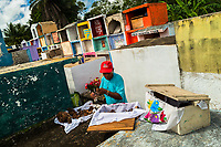 """A Mayan man cleans dried-up bones of a deceased family member during the bone cleansing ritual at the cemetery in Pomuch, Mexico, 27 October 2019. Every year on the Day of the Dead, people of Pomuch, a small Mayan community in the south of Mexico, visit the cemetery to take part in a pre-Hispanic tradition of cleaning of bones of their departed relatives (""""Limpia de huesos""""). People who die in Pomuch are firstly buried for three years in an above-ground tomb then the dried-up bodies are taken out, bones are separated, wrapped in a decorated cloth, put into a wooden crate, and placed on display among flowers for veneration."""
