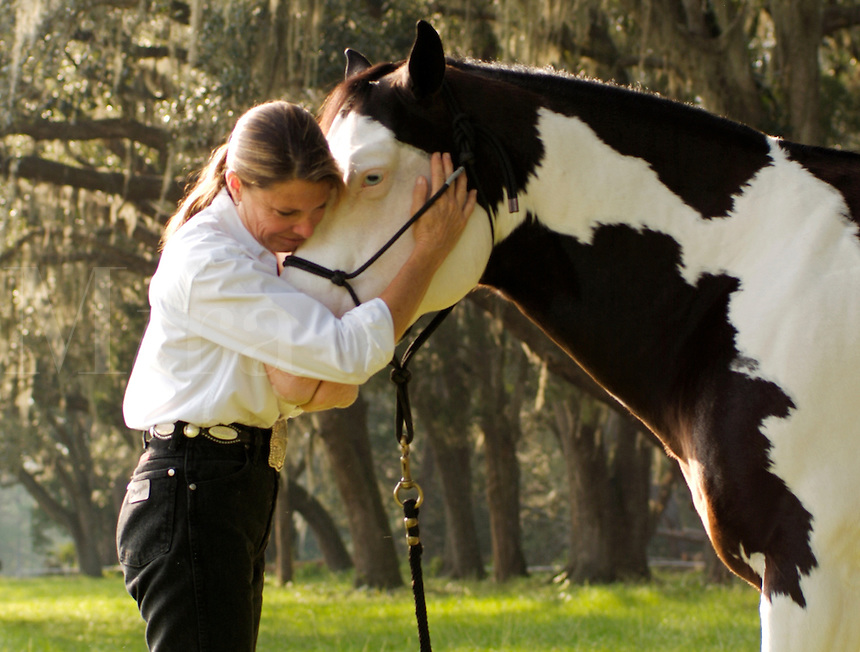 Middle Age American Indian woman hugs the face of her American Paint Horse stallion.