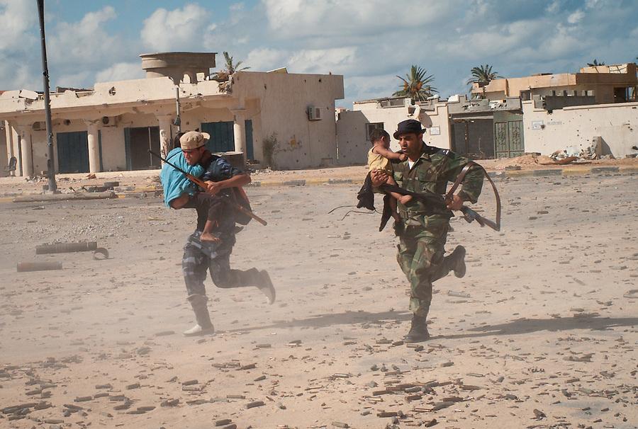 Anti-Gaddafi fighters run across the street under heavy sniper fire carrying Bangladeshi children trapped under siege in Sirte, Libya.
