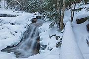 Stairs Falls on Dry Brook in New Hampshire's Franconia Notch in the White Mountains covered in snow. The Falling Waters Trail passes by this small waterfall.