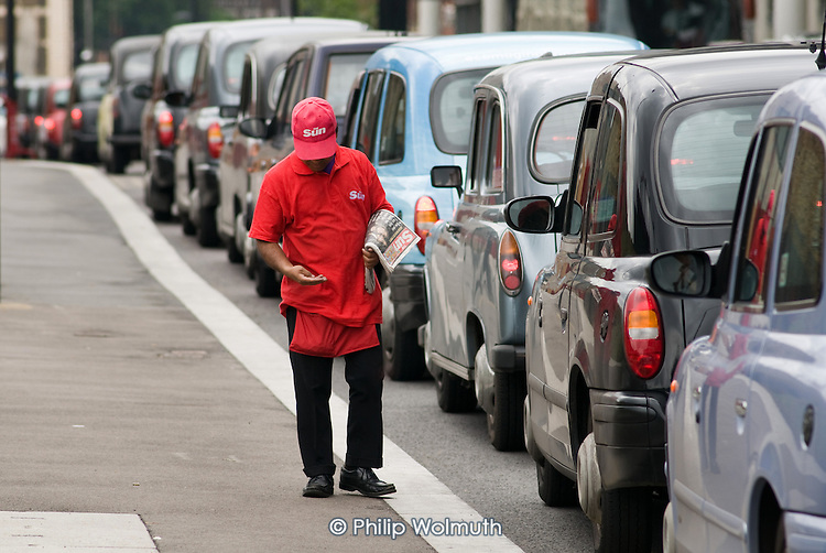A man sells The Sun newspaper at a taxi rank outside St.Pancras International station, London.