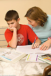 11 year old boy frustrated over homework assignment, mother talking him through it