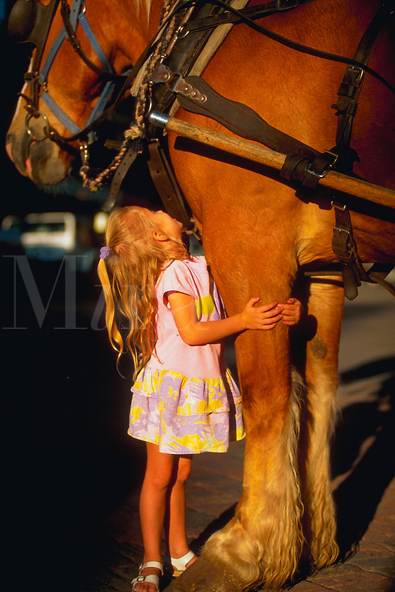 Little girl looking up adoringly at a horse as she hugs his leg.