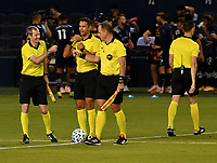 KANSAS CITY, KS - OCTOBER 07: The refereeing team, (L-R) Cory Richardson, Marcos de Oliveira and Brian Poeschel bump fists as they split off to their assignments before the match between Sporting KC and Chicago Fire FC before a game between Chicago Fire and Sporting Kansas City at Children's Mercy Park on October 07, 2020 in Kansas City, Kansas.