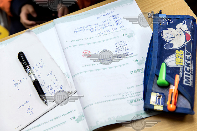 A fifth grad student's workbook lies on a desk during one of two ten minute recess periods amid their three hour long Saturday Mathematics Olympiad class at the Xueersi cram school. With their future success pinned on their academic performance at a very early age, Chinese students and their parents are under pressure to improve their academic performance in every perceivable way.