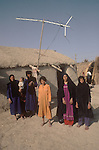 Marsh Arabs. Southern Iraq.  Marsh Arab women and children outside their adobe home with TV aerial banks of River Tigris... Haur al Mamar or Haur al-Hamar marsh collectively known now as Hammar marshes Iraq 1984