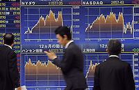 Businessmen pass the stocks board in Central Tokyo showing the latest stock prices in central Tokyo.  Stock prices have taken a battering all around the world as the financial crisis has deepened as the economic problems in Europe, especially Greece have come to the fore...............