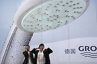 A man stretches out under an advertisement for German made bathroom wares at the International Building and Construction Trade Fair in Shanghai, China. China's continued building boom has made it the largest market in the world for building materials from end product like shower heads to raw material such as timber..