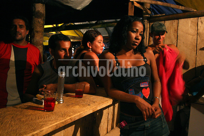 Women at a bar during the evening in a virtually instant town in the remote Amazon forest, about 80km from Apui in the Brazilian state of Amazonas, Feb. 1, 2007. Thousands of people have created the town, including prostitutes, bars and pharmacies, in a mobilization rivaling that of a military operation to dig for gold in the region, discovered in Dec. 2006. The environment is not much of a concern as trees are felled and pits are dug by people from all over Brazil and from all walks of life. Most simply say that some deforestation in the immense amazon it is the price to pay for Brazilians to exploit their nation's riches.  (FOTO:DOUGLAS ENGLE/AUSTRAL FOTO)