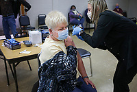 Shanna Workman, RN (right) administers a covid-19 vaccine to Mary Tompkins of Bella Vista (left), Friday, February 12, 2021 at Riordan Hall in Bella Vista. Community paramedics from the Bella Vista Fire Department administered second doses of the covid-19 vaccine to people in the 1-B category. Check out nwaonline.com/210213Daily/ for today's photo gallery. <br /> (NWA Democrat-Gazette/Charlie Kaijo)