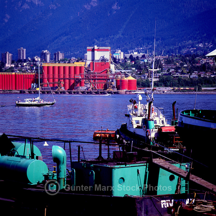 Industrial Waterfronts of Port of Vancouver, Vancouver, BC, British Columbia, Canada - Grain Elevators in North Vancouver and Tugboat along Vancouver Shore