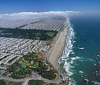aerial photograph of Ocean Beach, San Francisco, California; the Cliff House and Sutro Heights in the foreground, Golden Gate Park in the middle ground, and the Sunset district in the background