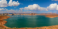 Colorful panorama on Lake Powell's turquoise water and orange rocks under a blue sky with white clouds, near Page, at the Arizona and Utah border, USA