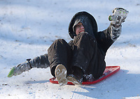 Gabe Newton, 9, of Prairie Grove laughs Friday, Feb. 19, 2021, as he makes his way downhill on a storage container lid while sledding with his family at Battlefield State Park in Prairie Grove. The Newtons were taking a break from virtual instruction to take advantage of the good sledding conditions before warm temperatures melted the snow from the hillside. Visit nwaonline.com/210220Daily/ for today's photo gallery. <br /> (NWA Democrat-Gazette/Andy Shupe)