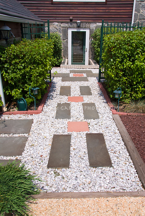 Entrance to house made more appealing with simple flagstone and pebble path and tier of plants and shrubs allee. Think Viburnum shrubs, with juniper at front left