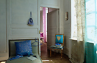 A chaise longue and a gilt-framed chair are placed beside an open door leading through to a pink bedroom