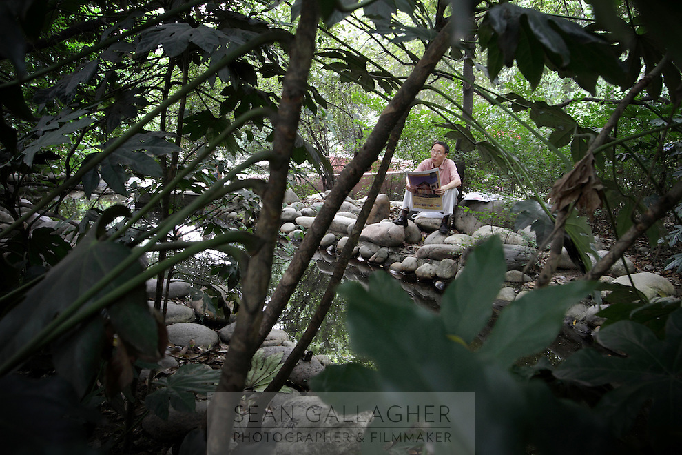 """A man reads a newspaper in the """"Living Water Garden"""" in Chengdu, Sichuan Province. The garden is a park aimed at highlighting the importance of the relationship between man and water. 2010"""