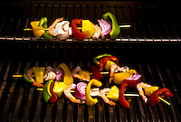 Shrimp kebabs with red, green and yellow peppers, pineapple, red onion and mushrooms on gas grill, poolside.