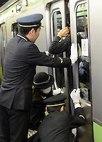 Railway staff  try to release a mans arm trapped by a door on a full train during rush hour, Shinjuku Station, Tokyo, Japan. With up to 4 million passengers passing through it every day, Shinjuku station, Tokyo, Japan, is the busiest train station in the world. The station was used by an average of 3.64 million people per day.  That's 1.3 billion a year.  Or a fifth of humanity. Shinjuku has 36 platforms, and connects 12 different subway and railway lines.  Morning rush hour is pandemonium with all trains 200% full. <br /> <br /> Photo by Richard jones / sinopix