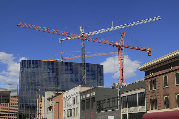 Construction cranes raising new buildings next to older downtown,  Denver, Colorado, USA. .  John leads private photo tours in Boulder and throughout Colorado. Year-round Colorado photo tours.