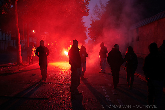 Protester light a red flare during a demonstration in Paris, France on Oct. 19, 2010. A proposal to reform pensions in France by raising the retirement age from 60 to 62 kicked off strikes and major protests against the Sarkozy government's austerity measures.