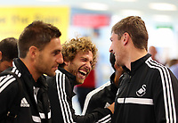 Wednesday 07 August 2013<br /> Pictured: Jose Canas (C) and Ben Davies (R) share a joke while queuing to check in at Cardiff Airport.<br /> Re: Swansea City FC travelling to Sweden for their Europa League 3rd Qualifying Round, Second Leg game against Malmo.