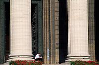 Man reading a book beside the columns of La Madeleine church, Paris, France.