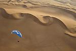 Deddeda paraglides over sand dunes in Iquique, Chile.