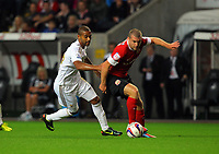 Pictured L-R: Luke Moore of Swansea challenging Stephen Dawson of Barnsley. Tuesday 28 August 2012<br /> Re: Capital One Cup game, Swansea City FC v Barnsley at the Liberty Stadium, south Wales.