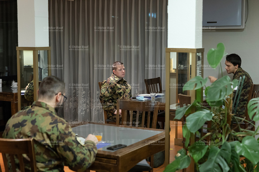 """Switzerland. Canton Ticino. Losone. Hotel Garni Tiziana. Three soldiers / tow men and a woman) dressed with camouflage uniform seat at the breakfast room. Due to the spread of the coronavirus (also called Covid-19), the Federal Council has categorised the situation in the country as """"extraordinary"""". The army was called upon to provide its troops in terms of medical assistance. The militia soldiers from medical troops were called by the Swiss army for the first time since World War II. Under the country's militia system, professional soldiers constitute a small part of the military and the rest are conscripts or volunteers aged 19 to 34 (in some cases up to 50). They will be on duty the all day at the Ospedale Regionale di Locarno La Carità. 20.11.2020 © 2020 Didier Ruef"""