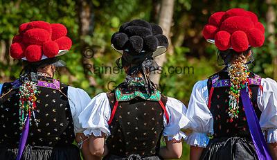 Deutschland, Baden-Wuerttemberg, Ortenaukreis, Kirnbach (Wolfach): drei junge Frauen auf dem Kirnbacher Bollenhut-Talwegle in der beruehmten Kirnbacher Tracht mit dem roten und schwarzen Bollenhut, die heute in der ganzen Welt als Schwarzwaelder Tracht bekannt ist - Rueckansicht   Germany, Baden-Wurttemberg, Kirnbach (Wolfach): three young women in famous Black Forest costume with red and black Bollenhat - back view