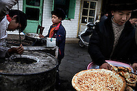 Uighur men bake flat bread (nan) in a barrel oven in the Old City section of Kashgar, Xinjiang, China.